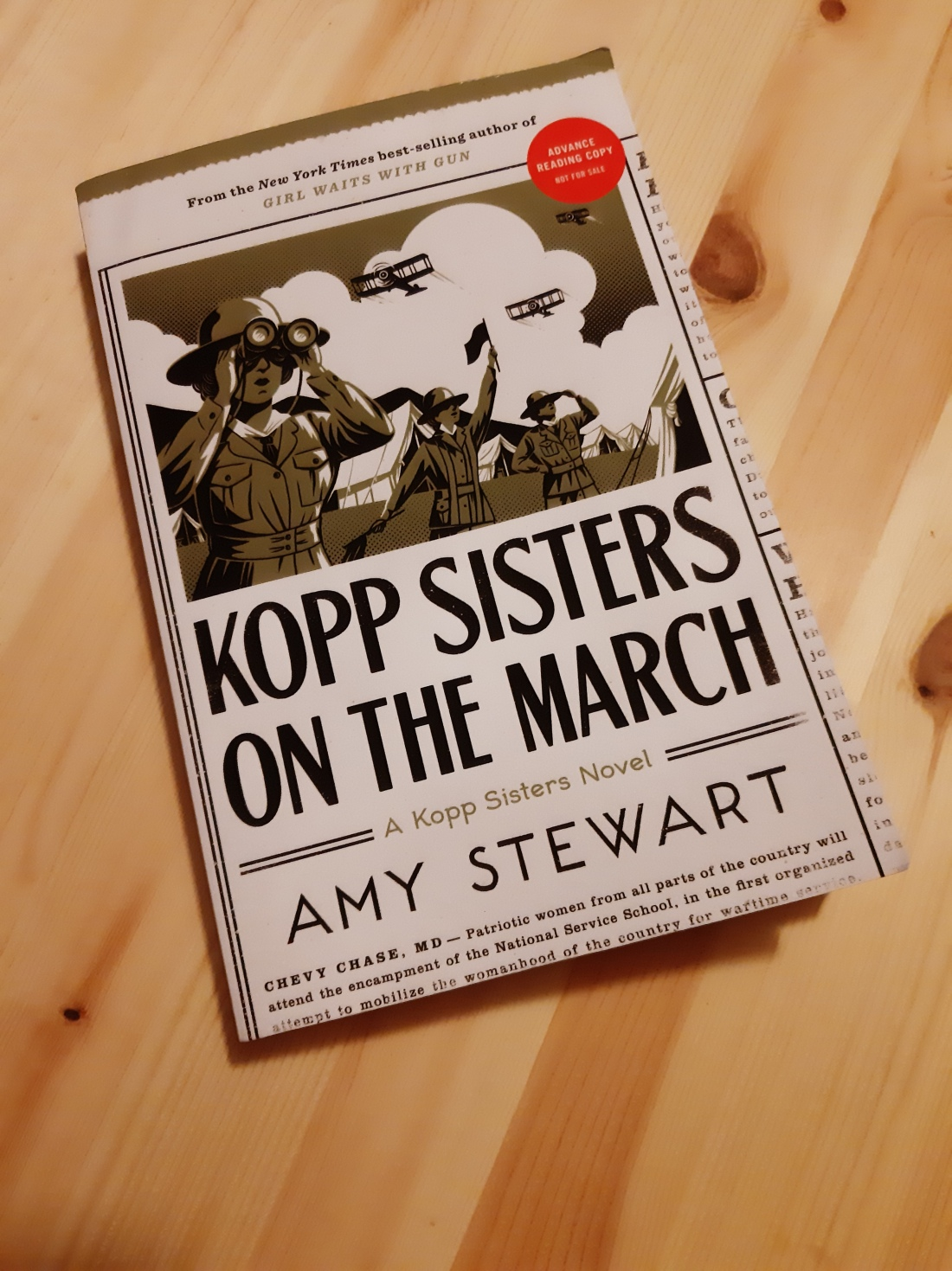 Advance paperback copy of Kopp Sisters on the March by Amy Stewart against a wooden background. Cover art shows three women in military-style dress in an outdoor area, biplanes in the sky and tents on the grounds surrounding them. The woman in the foreground holds binoculars to her eyes, the woman in the middle ground raises signaling flags, and the woman in the background holds a hand up to her hat as if surveying the goings-on of the camp.