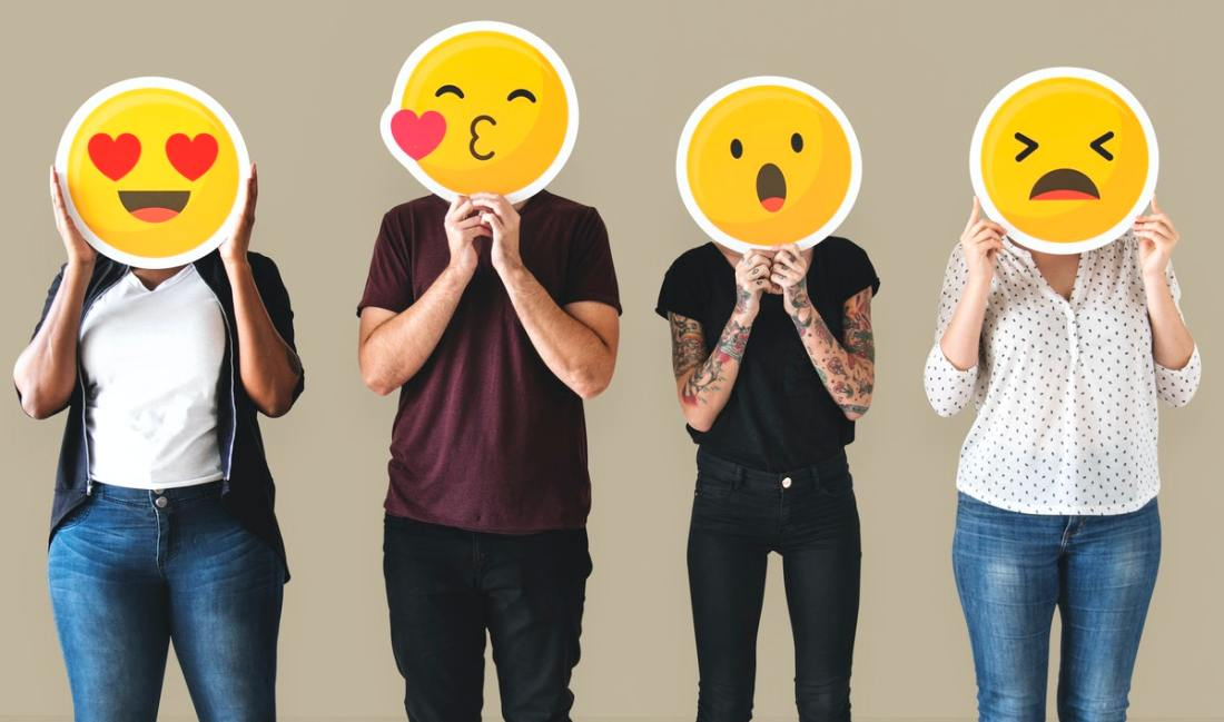Diverse people, with faces covered with emoticons